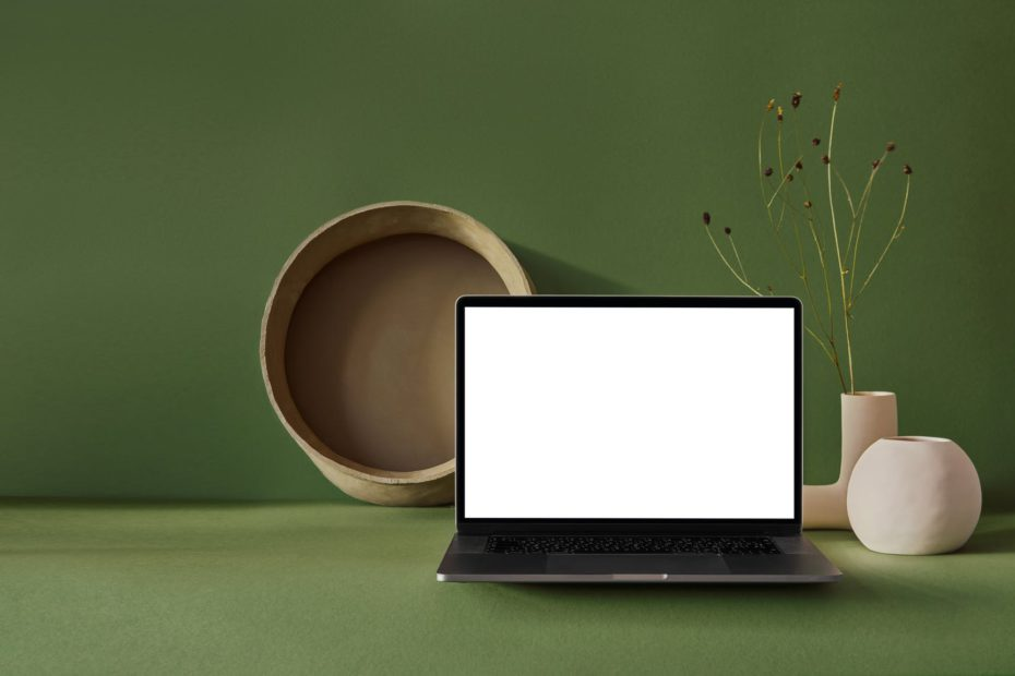 workplace with laptop and ceramic vase with basket